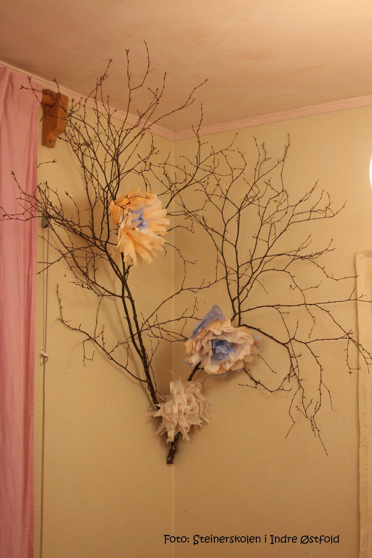 Store papirblomster hengende fra gren i 1.klasserommet på Steinerskolen